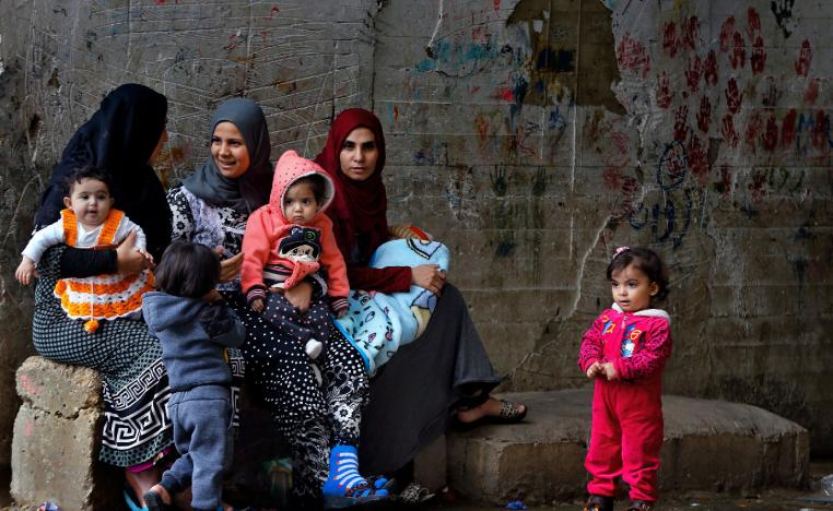Syrian refugees women hold their children as they sit in Ouzai refugee compound, in the southern port city of Sidon, Lebanon.