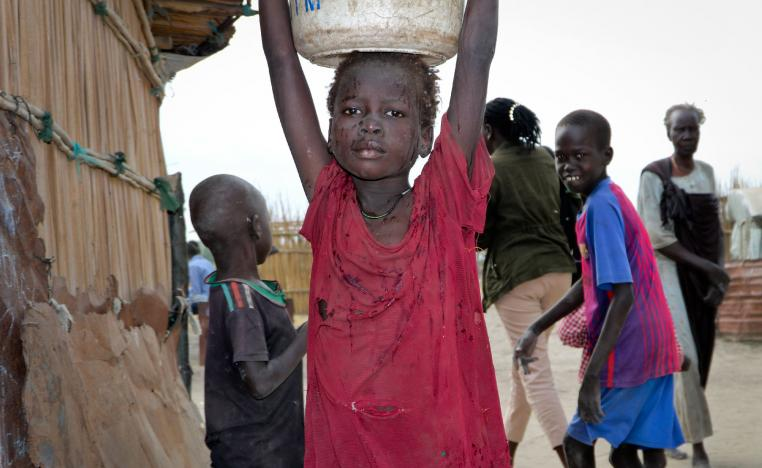 A young girl carries water on her head in Koythiey displaced person's camp on the outskirts of Bentiu town in South Sudan.