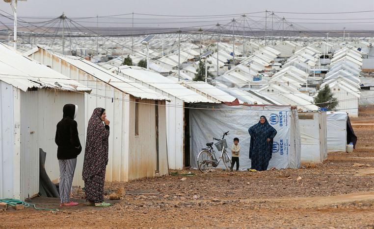 Syrian refugee women stand in front of their homes at Azraq refugee camp, near Al Azraq city, Jordan