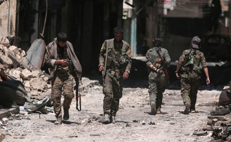 Syria Democratic Forces (SDF) fighters walk on the rubble of damaged shops and buildings in the city of Manbij, in Aleppo Governorate, Syria, August 10, 2016.