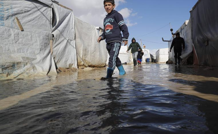 A child wades through rain and snow waters at an informal tent settlement housing Syrian refugees following winter storms in the area of Delhamiyeh, in the central Bekaa Valley on January 17, 2019.