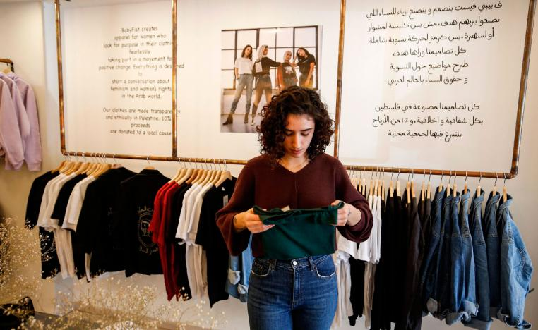 "Palestinian fashion designer Yasmeen Mjalli speaks while standing in her clothing shop where her label collection ""BabyFist"" carrying anti-sexual harassment slogans is showcased, in Ramallah in the Israeli-occupied West Bank on December 19, 2018."