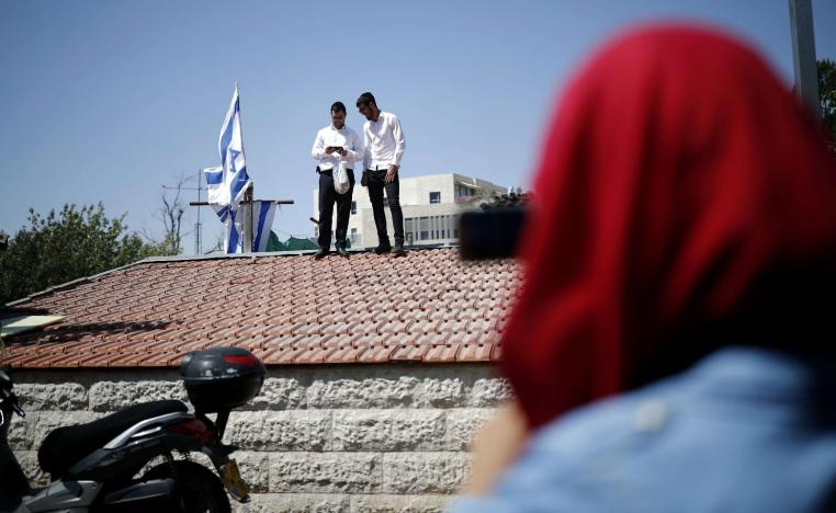 Religious Jewish men stand on the roof of a house seized by new Jewish owners in the Arab neighbourhood of Sheikh Jarrah in east Jerusalem on September 8, 2017, which originally belonged to the Palestinian Shamasneh family in which they lived for over half a century, until they were evicted on September 5.