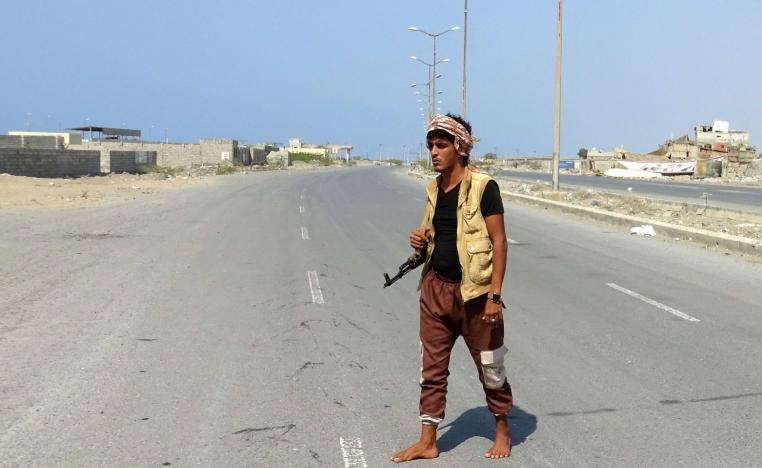 A member of the Yemeni pro-government forces walks with his rifle at the eastern entrance of the port city of Hodeidah on December 30, 2018