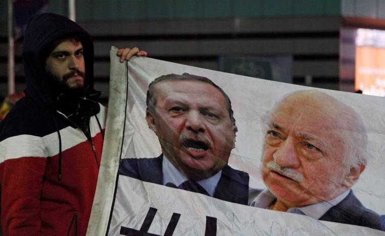 A demonstrator hold pictures of Turkey's Prime Minister Tayyip Erdogan and Turkish cleric Fethullah Gulen.