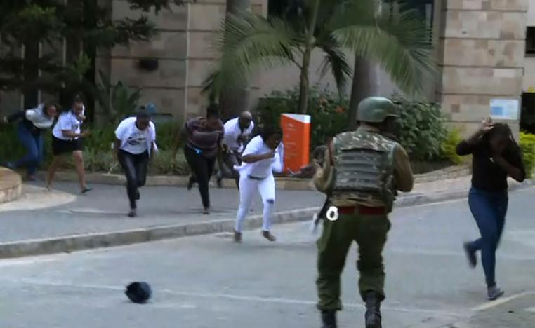 Image taken from an AFP TV footage shows people running in a street as a gunfight was underway following a blast at a hotel and office complex in a leafy Nairobi neighbourhood on January 15, 2019.