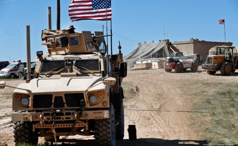A US soldier, left, sits on an armored vehicle in Manbij, northern Syria.
