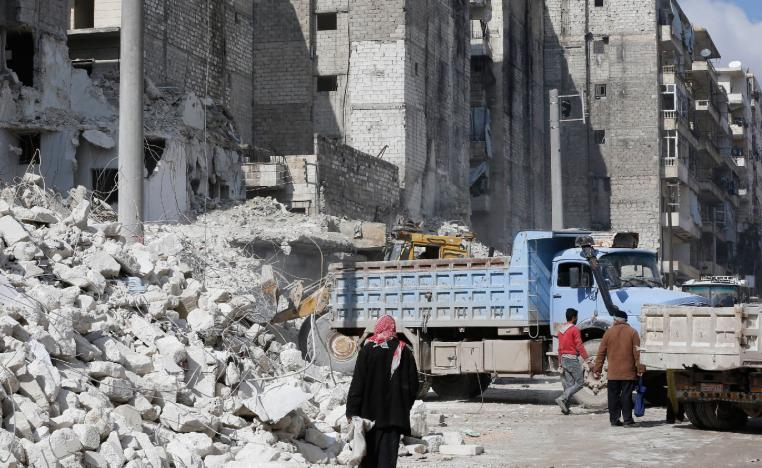 A tractor and trucks remove the rubble from buildings that were heavily damaged or destroyed during battles between rebel fighters and regime forces, in the former opposition held district of Salaheddin in the northern Syrian city of Aleppo on February 11, 2019.