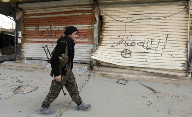 """A fighter from the Syrian Democratic Forces (SDF) walks past shops with their fronts painted with the Arabic phrases """"beware a sniper"""" and """"caliphate state"""", in the city of Hajin in Syria's eastern Deir Ezzor province on January 27, 2019."""