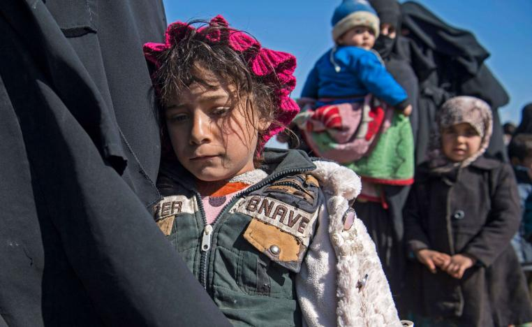 Women and children stand in a field after they fled from the Baghouz area in the eastern Syrian province of Deir Ezzor on February 12, 2019 during an operation by the US-backed Syrian Democratic Forces (SDF) to expel hundreds of Islamic State group (IS) jihadists from the region.