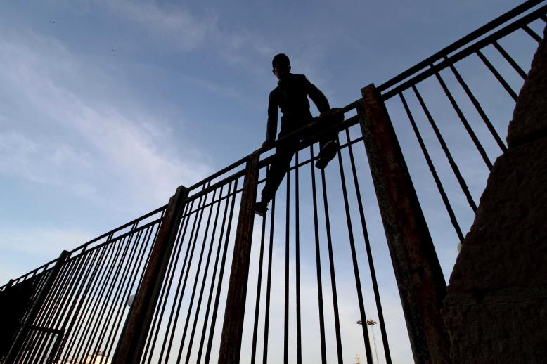 Moroccan youngster climbs a fence in the port of the Spanish enclave of Melilla bordering Morocco