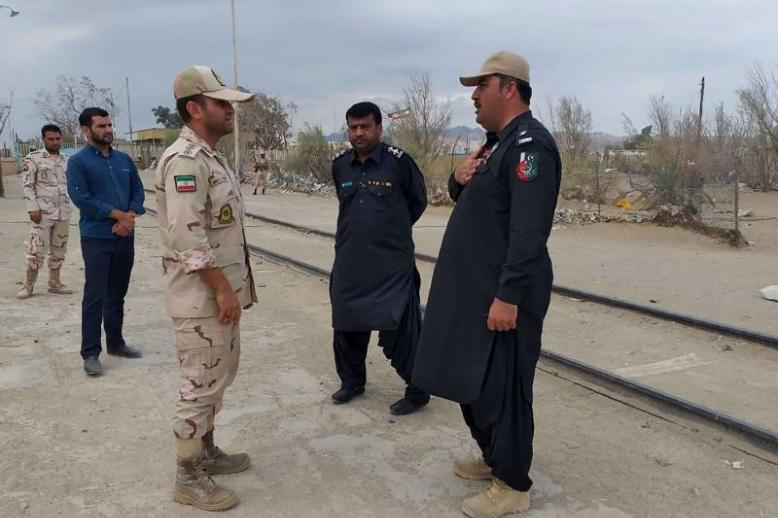 A Pakistani border security official (R) and an Iranian border official meet at Zero Point in the Pakistan-Iran border town of Taftan, on October 16