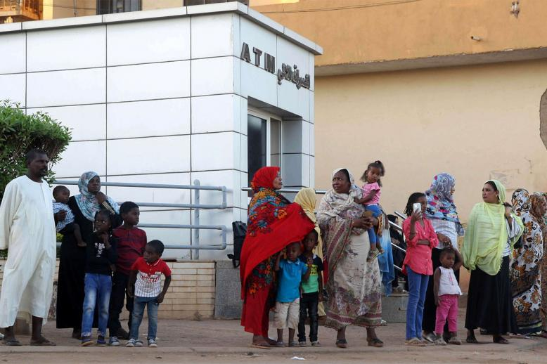 Residents stand outside an automated teller machine (ATM) in Khartoum