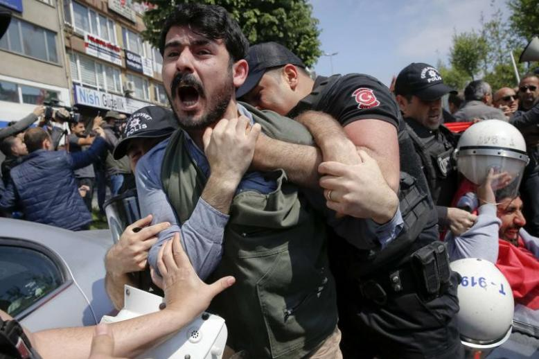 A demonstrator screams as police officers grab him during a protest in Istanbul