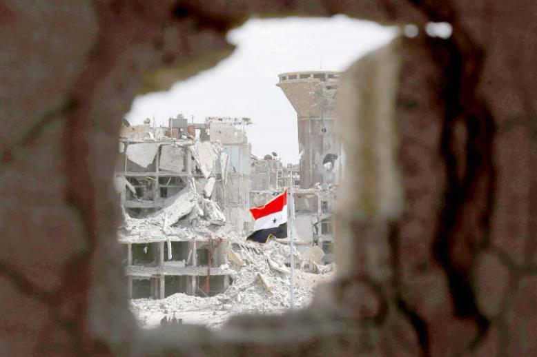 A Syrian flag flies in a rubble strewn street at the entrance of the Hajar al-Aswad neighbourhood on the southern outskirts of Damascus