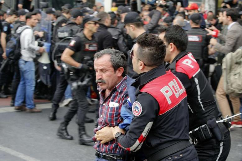 Police officers detain a Turkish man during protests in Istanbul, last May