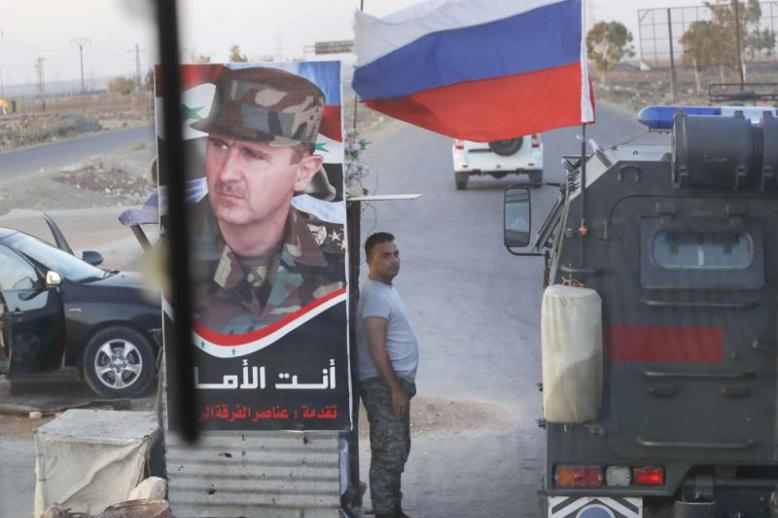 A shift in direction. A Syrian soldier stands at a checkpoint as a Russian military police vehicle passes by near the village of Almajdiyeh, last August.
