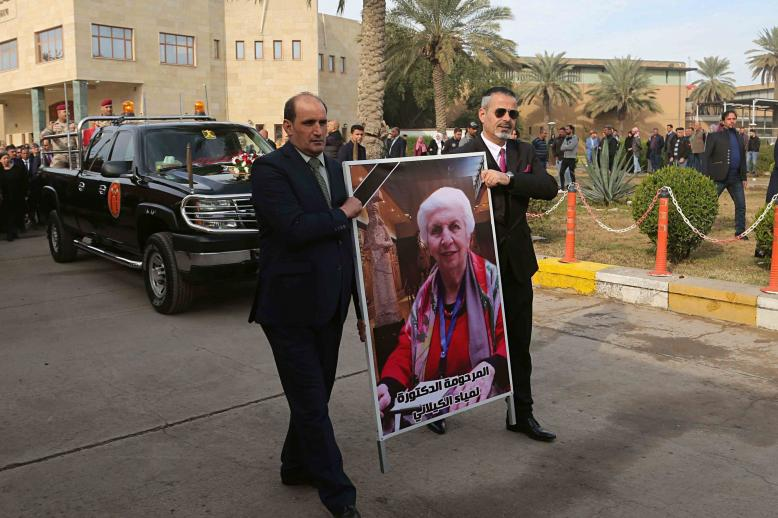 Mourners transport the flag-draped coffin of Iraqi archaeologist, Lamia al-Gailani, seen in the poster, for burial during her funeral procession in the National Museum in Baghdad, Iraq, Monday, Jan. 21, 2019