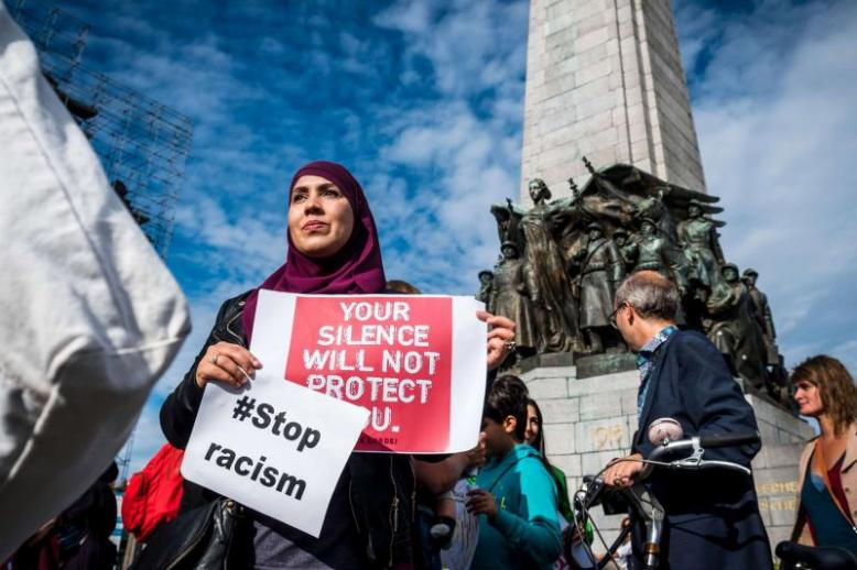 A Muslim woman holds posters as she protests against 'hate and islamophobia' in Brussels, last September 9