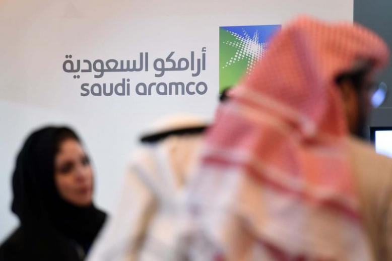 Engine of growth. Saudi and foreign investors stand in front of the logo of Aramco in Riyadh
