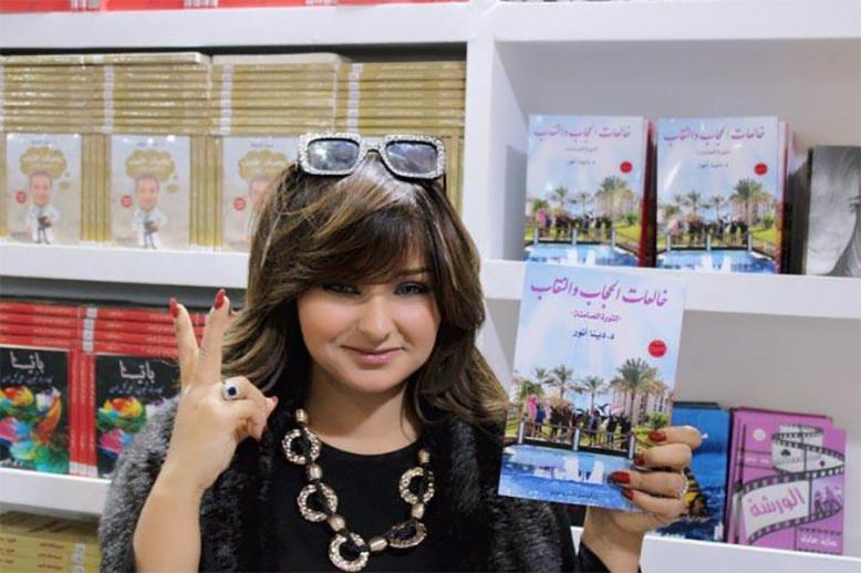 "Dena Anwer holding her book ""Those Taking Off the Hijab: The Silent Revolution"""