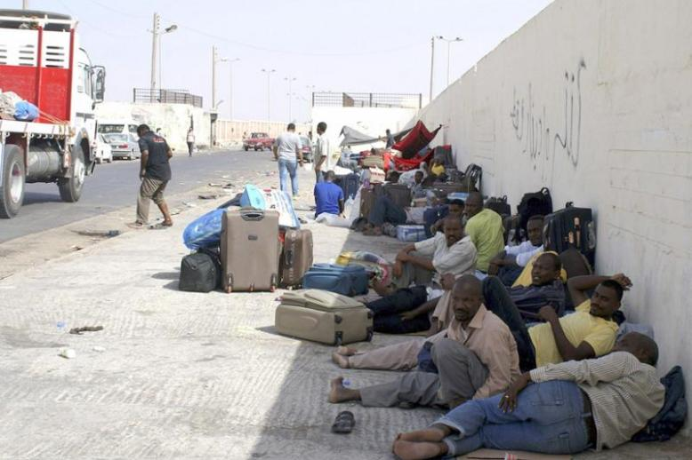 Another useless wall? Sudanese workers rest as they wait for Egyptian visas next to the Libyan-Egyptian border crossing in Musaid.
