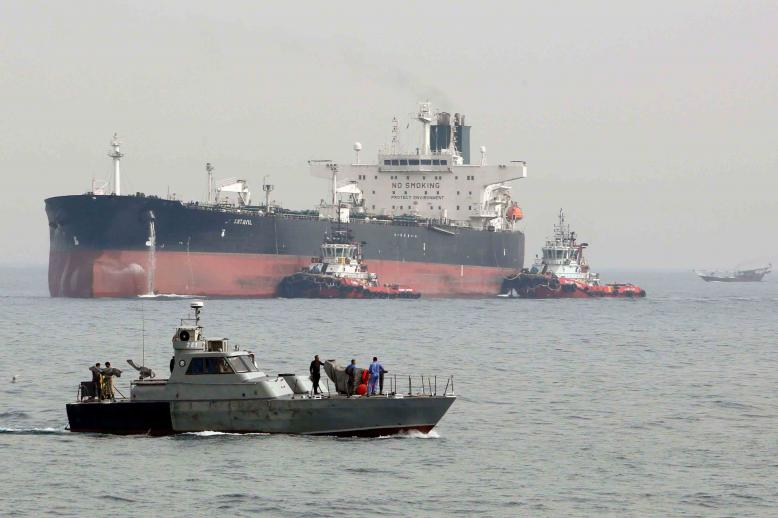 An Iranian military speedboat patrols the waters as a tanker prepares to dock at the oil facility in the Khark Island, Iran