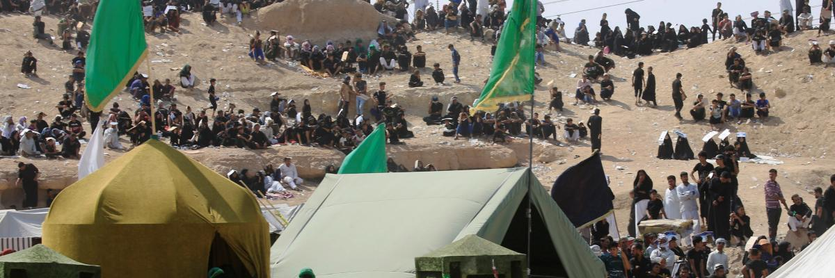Iraqi people behind tents watch the local actors dressed as ancient warriors re-enact a scene from the 7th century battle of Karbala to commemorate Ashura in Najaf, September 20, 2018.