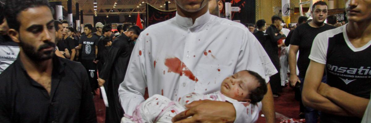 A man holds a baby as Shiite Muslims flagellate themselves during the ten-day mourning period leading up to Ashura, on September 19, 2018 in Iraq's holy city of Najaf.