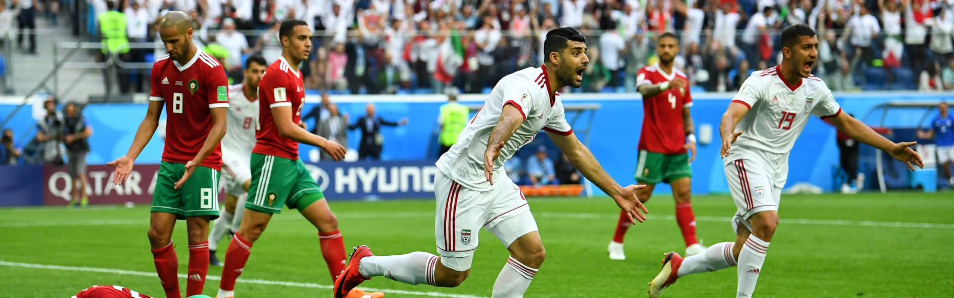 Morocco's Aziz Bouhaddouz looks dejected after scoring an own goal for Iran's first goal as Iran's Mehdi Taremi and Majid Hosseini celebrate.