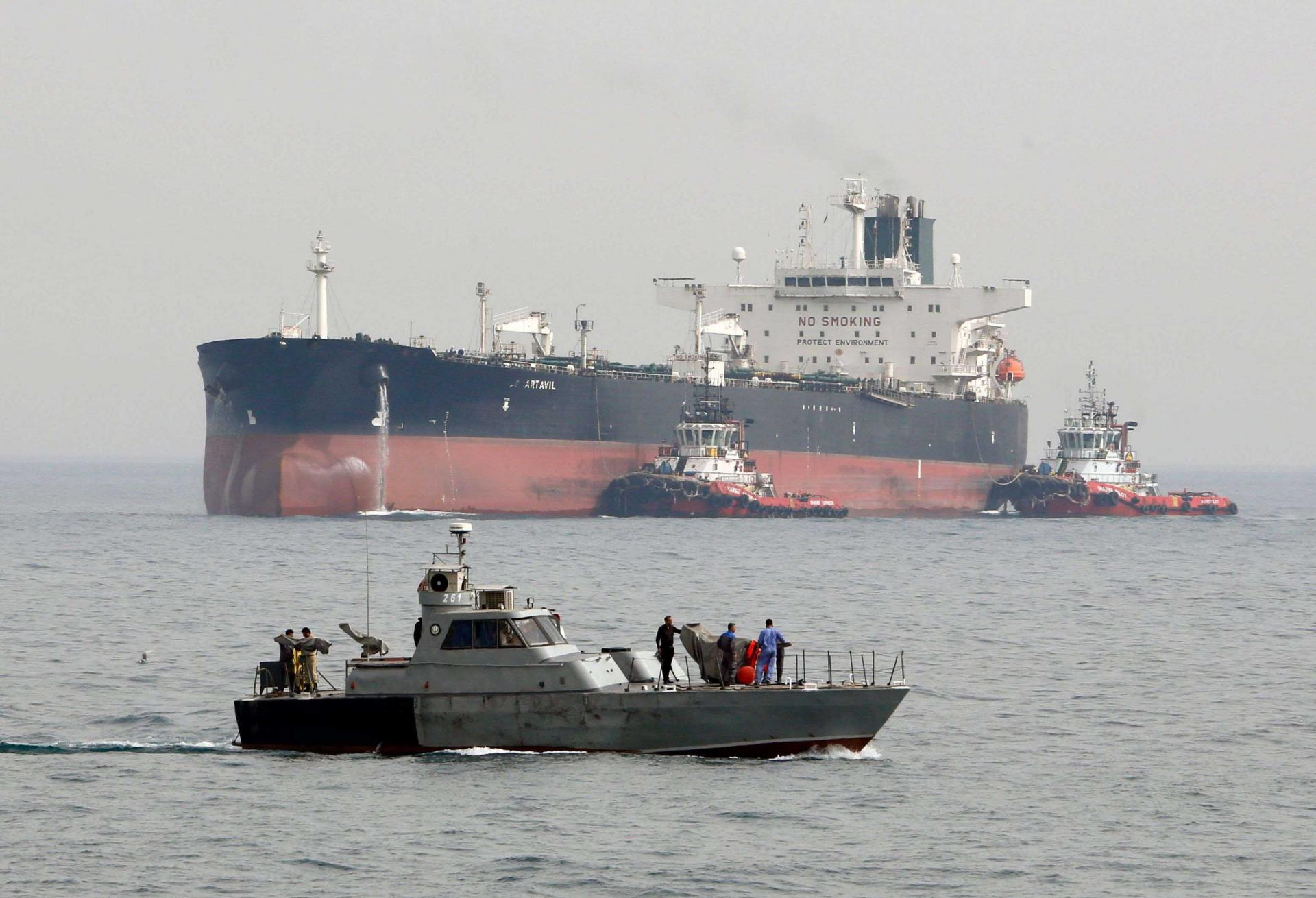 An Iranian military speedboat patrols the waters as a tanker perpares to dock at the oil facility in the Khark Island