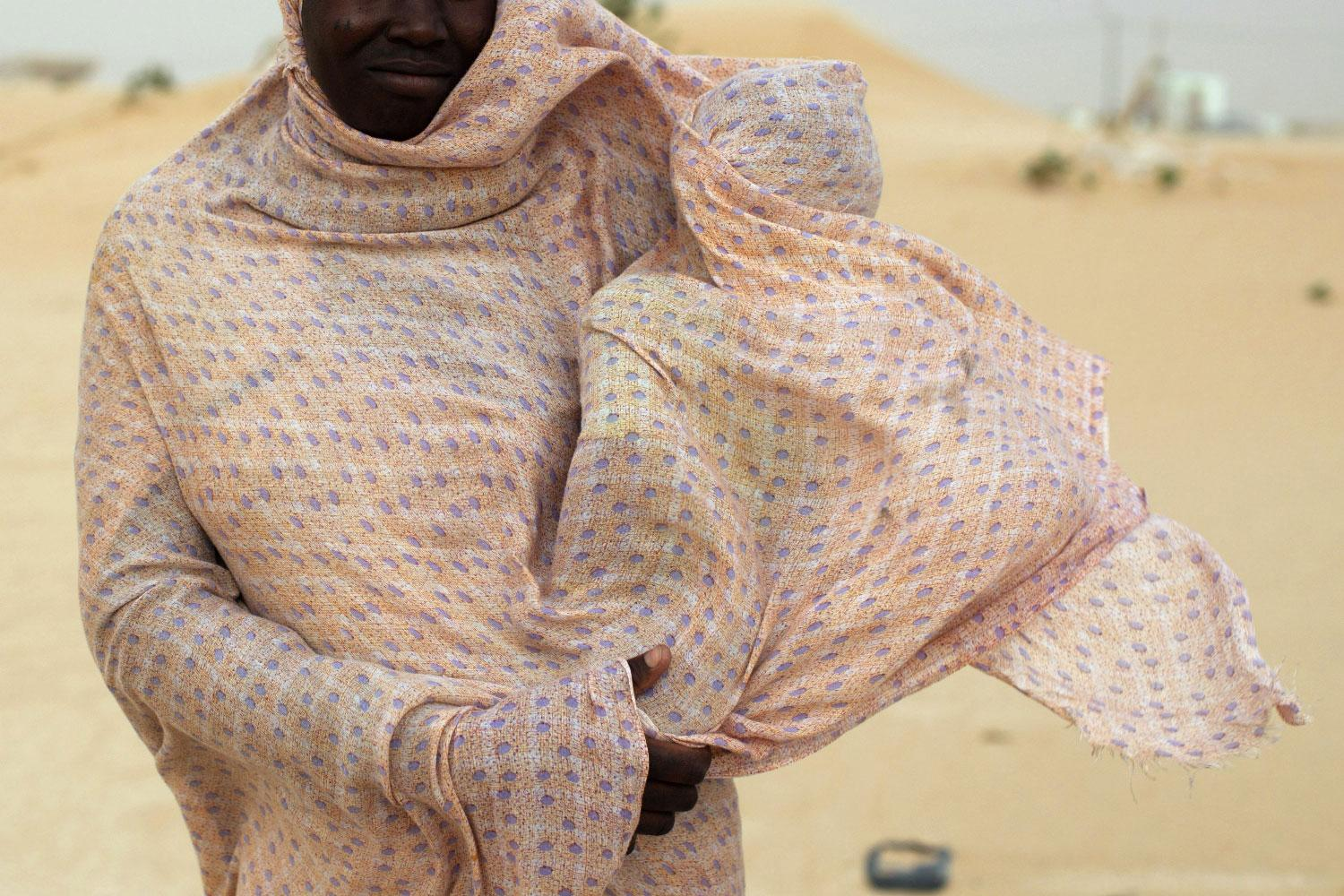 A woman shields her child from the wind while walking on sand dunes near Nouakchott, Mauritania.