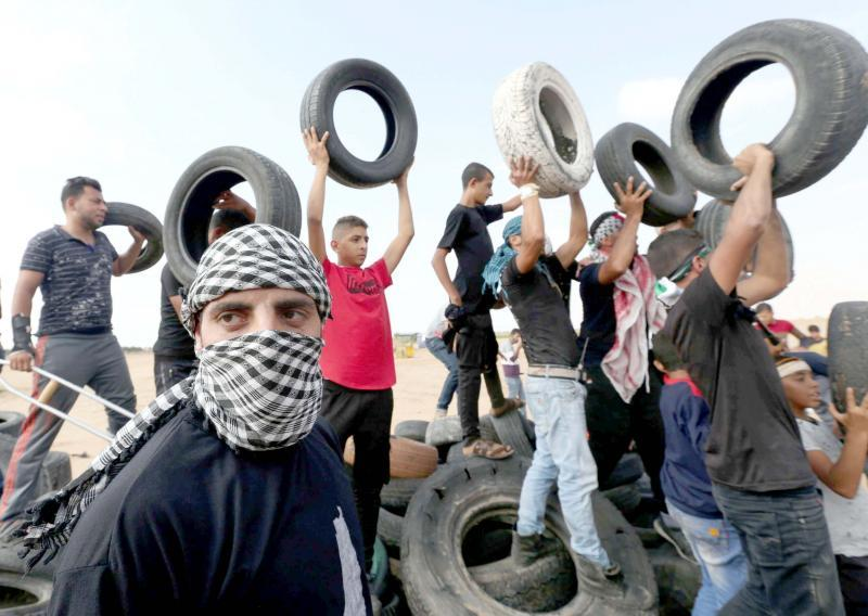 Palestinian demonstrators hold tyres during a protest at the border fence in southern Gaza, on October 19
