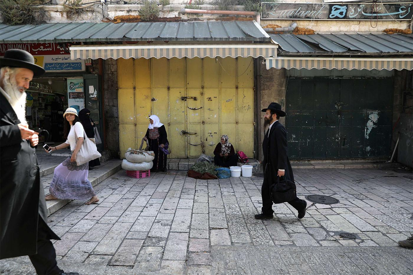 People walk past closed shops during a general strike in Jerusalem's Old City