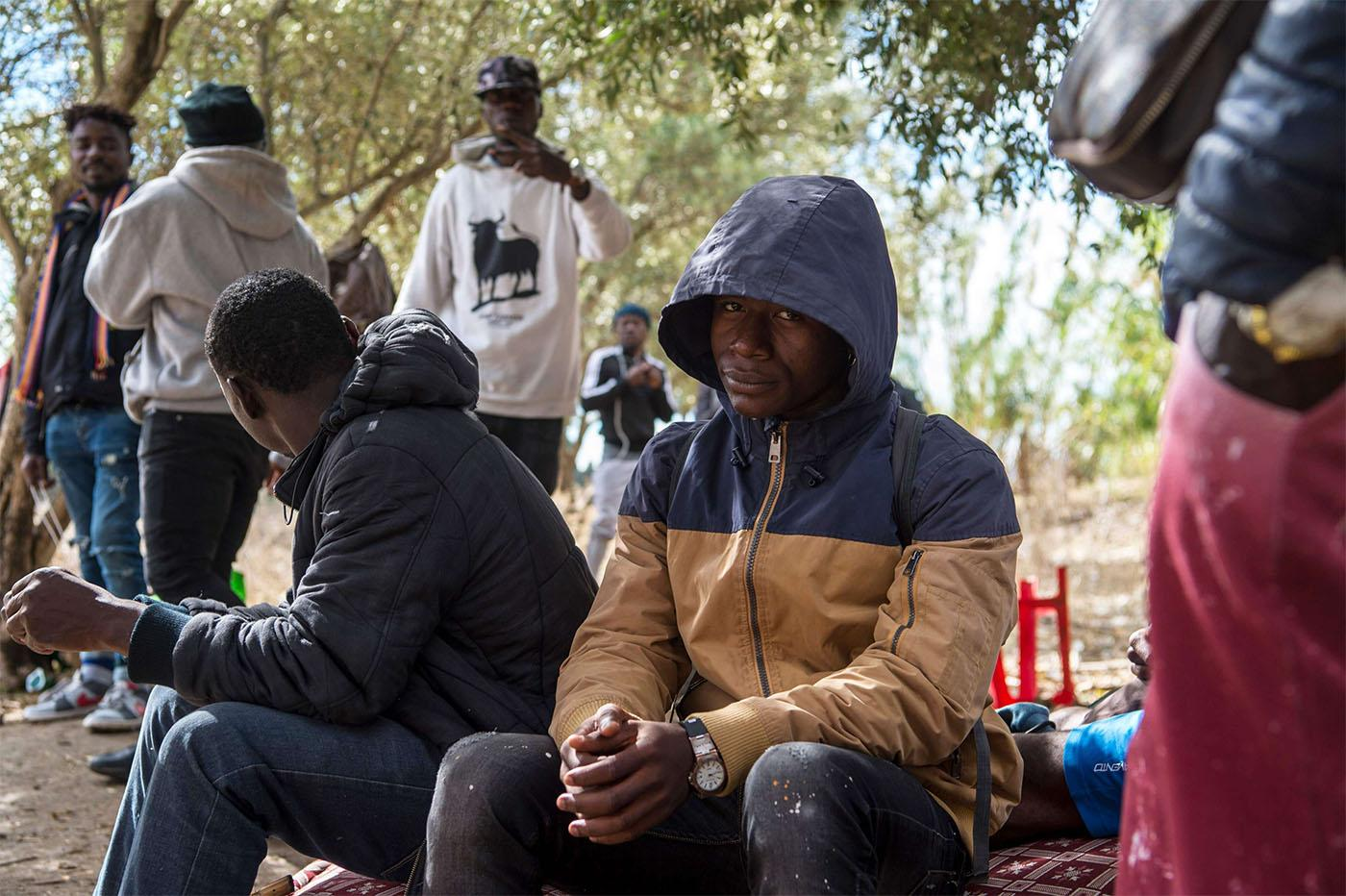 Migrants from Sub-Saharan Africa take shelter while hiding from the police in a forest in the district of Boukhalef of Tangiers