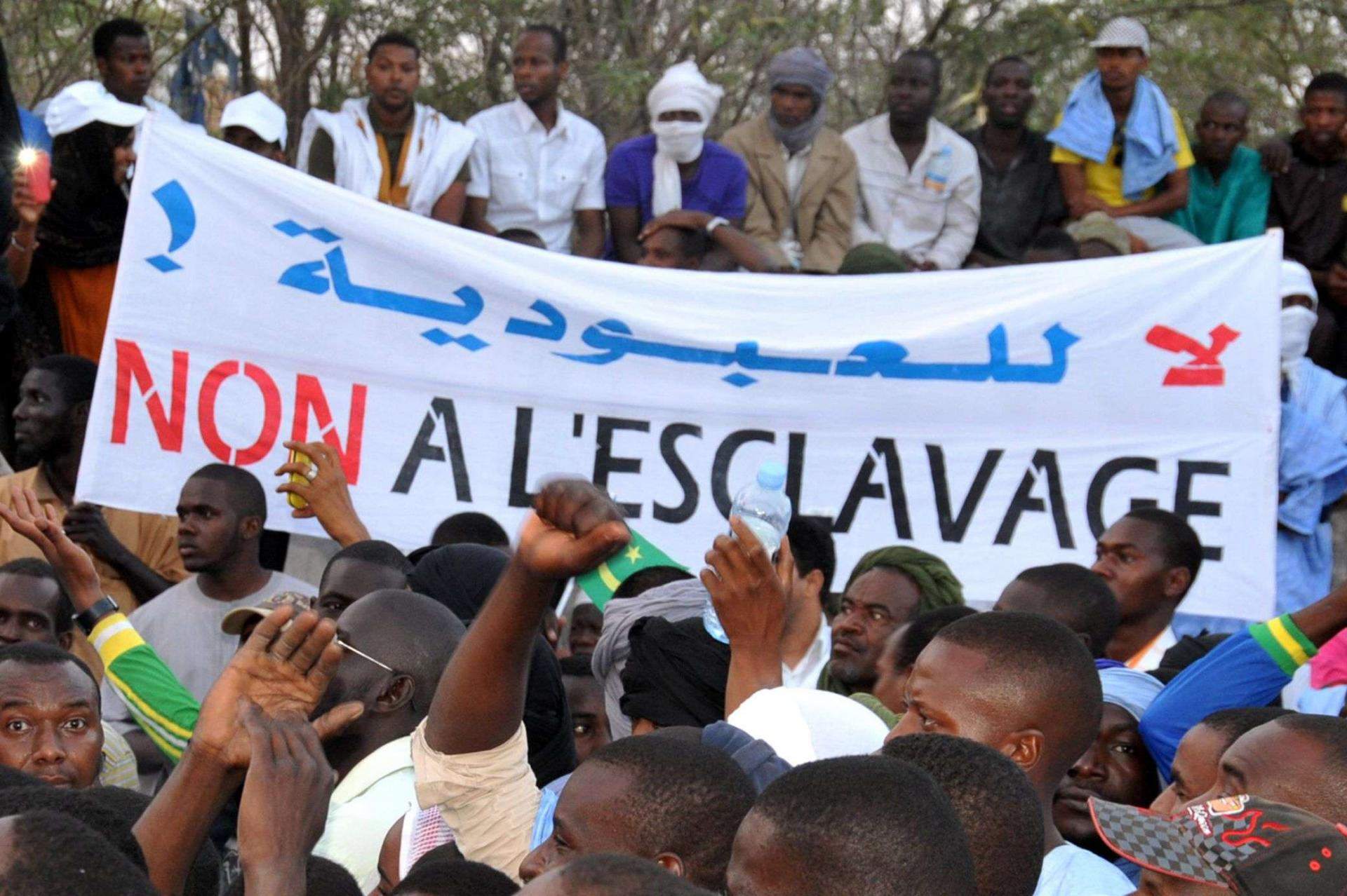 """People holding a banner reading """"No to slavery"""" during a demonstration against discrimination in Nouakchott, Mauritania."""
