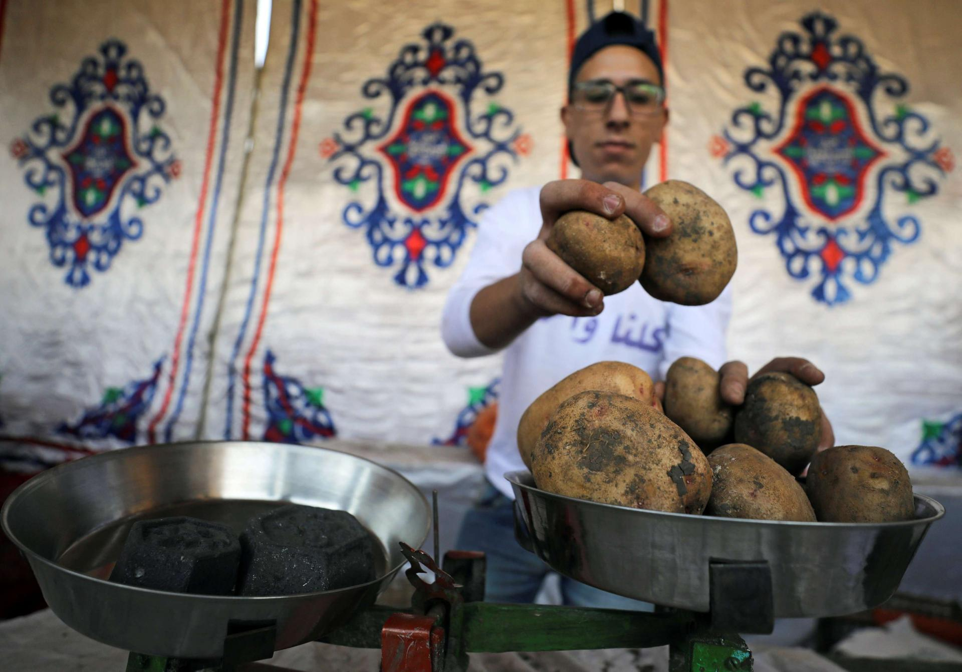 A vendor weighs potatoes at a temporary tent with government subsidised goods, after consumer prices increase across the country in Cairo, Egypt.