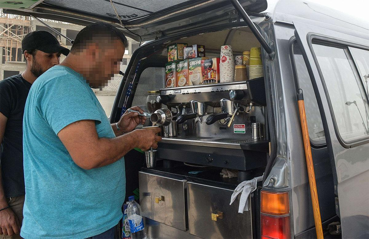 A Syrian refugee prepares coffee at the back of an improvised food truck in the Egyptian capital Cairo