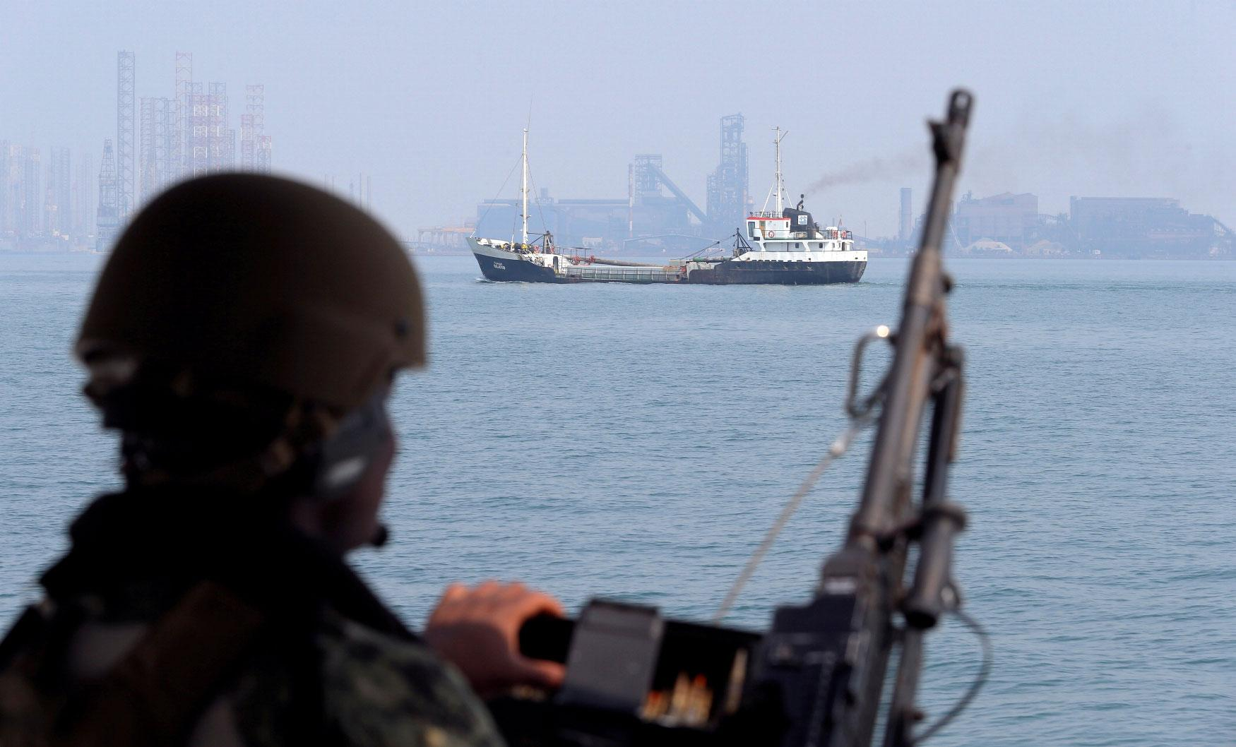 US Navy soldier stands guard as an oil tanker sails past.
