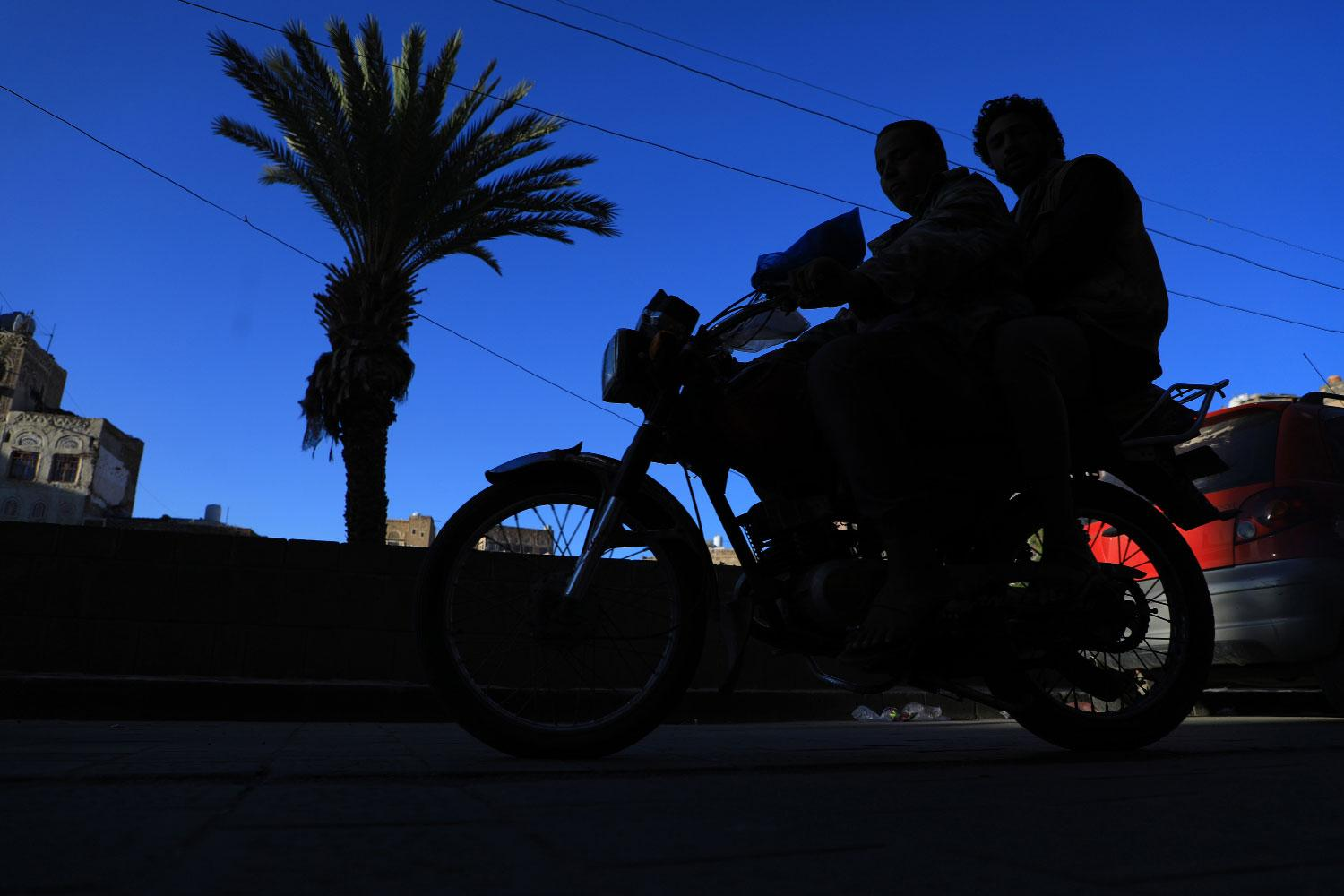 Yemenis ride a motorbike past historical buildings in the old quarter of the capital Sanaa on November 14, 2018.