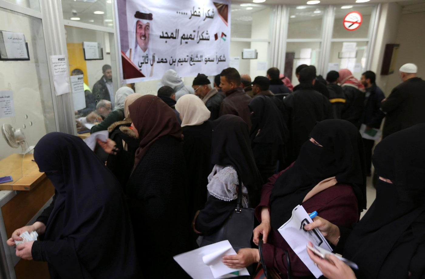 Palestinian Hamas-hired civil servants wait to receive their salaries paid by Qatar as a banner showing a picture of Qatar's Sheikh Tamim bin Hamad Al Thani is seen, in Khan Younis in the southern Gaza Strip December 7, 2018.