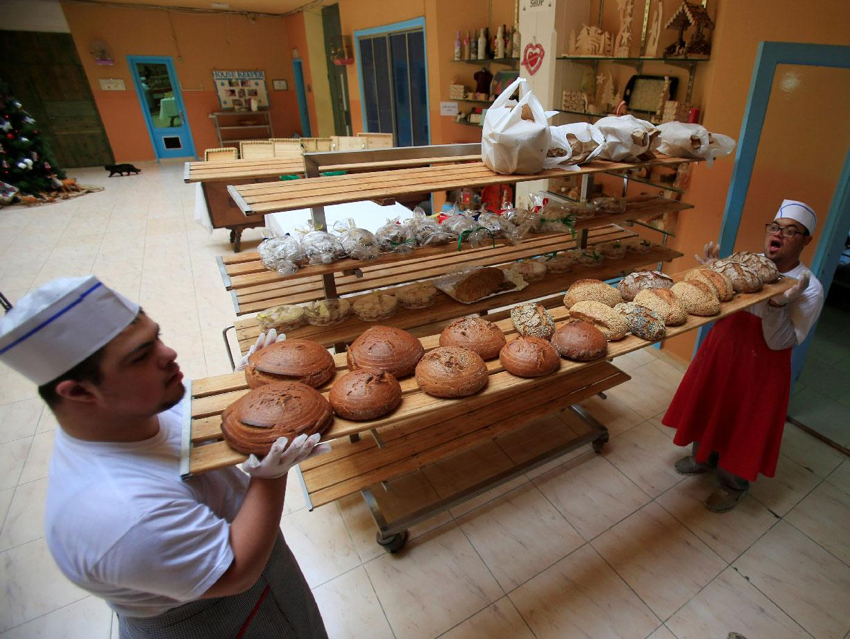 Men with special needs hold bread in the southern city of Tyre, Lebanon December 18, 2018.