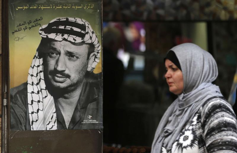 A Palestinian woman walks past a portrait of late leader Yasser Arafat in the West Bank city of Ramallah