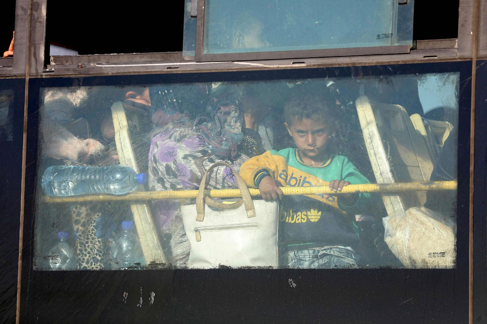 A Syrian child looks through the windows of a bus as displaced people from the Quneitra province wait at the Murak crossing point to be carried in the provinces of Idlib and Aleppo, in Murak, northwestern Syria, on July 21, 2018.