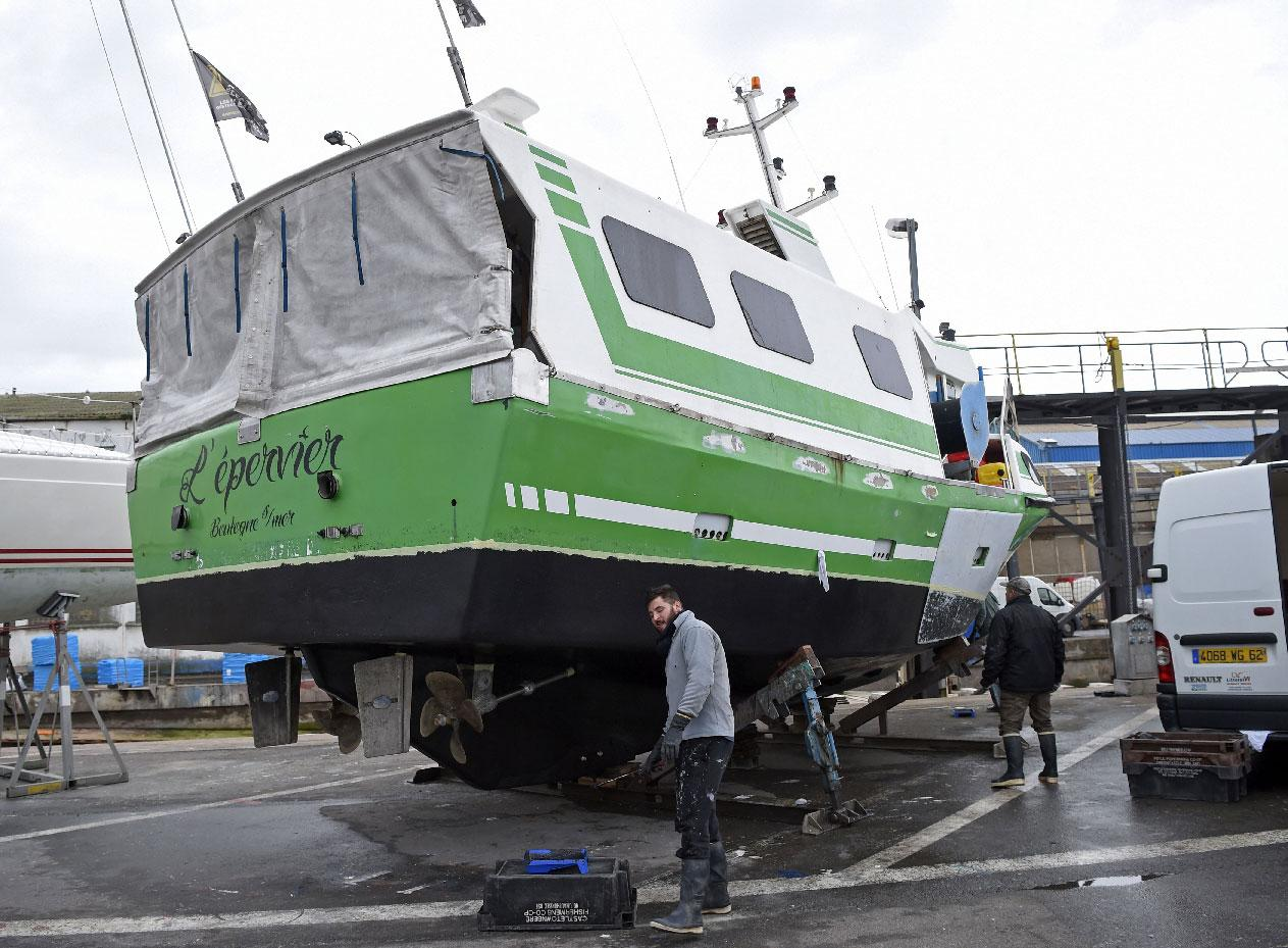 """French workers repair """"L'Epervier"""" on November 29, 2018, a boat that was stolen and damaged by migrants who tried to cross the English Channel, in Wissant, northern France."""