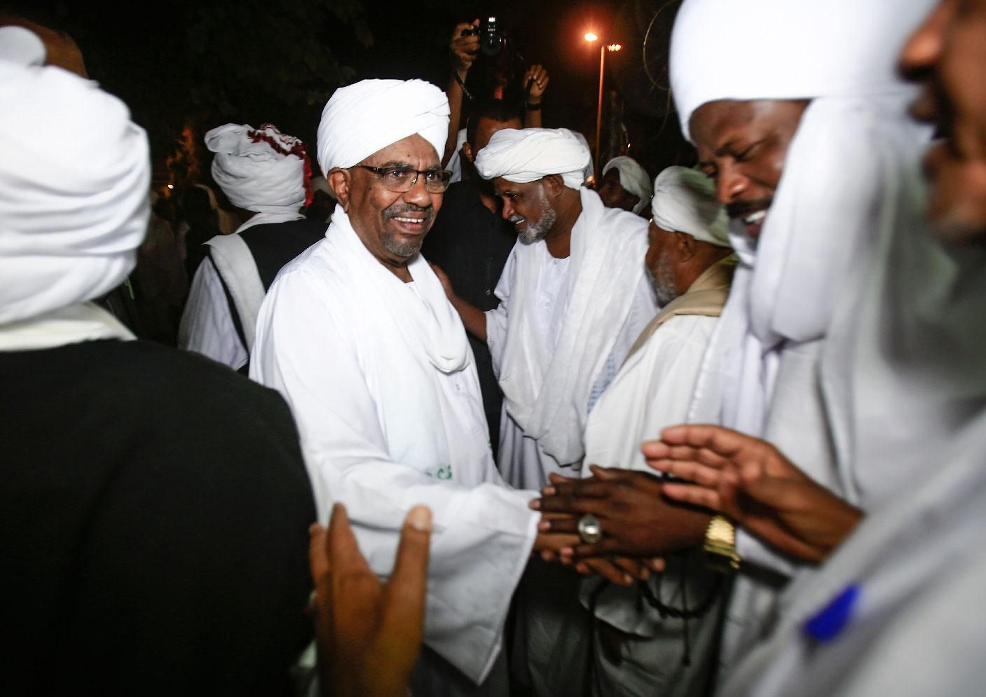 Sudanese President Omar al-Bashir shakes hands with Sufi Muslim clerics at the presidential palace in the capital Khartoum on January 3, 2019.