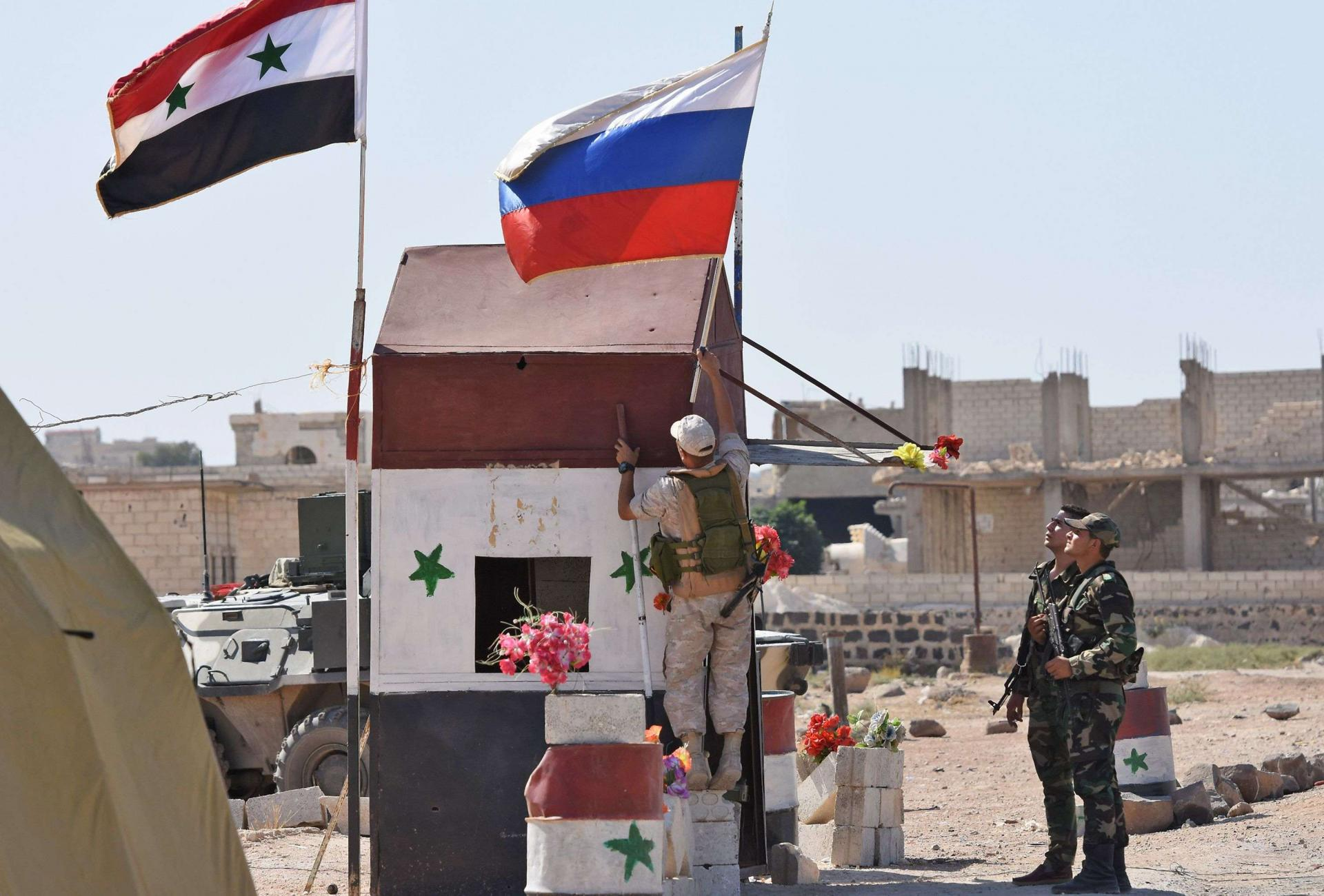 Russian soldiers place the national flag at the Abu Duhur crossing on the eastern edge of Idlib province on September 25, 2018, as Syrian families cross from rebel-held areas to regime-held areas.