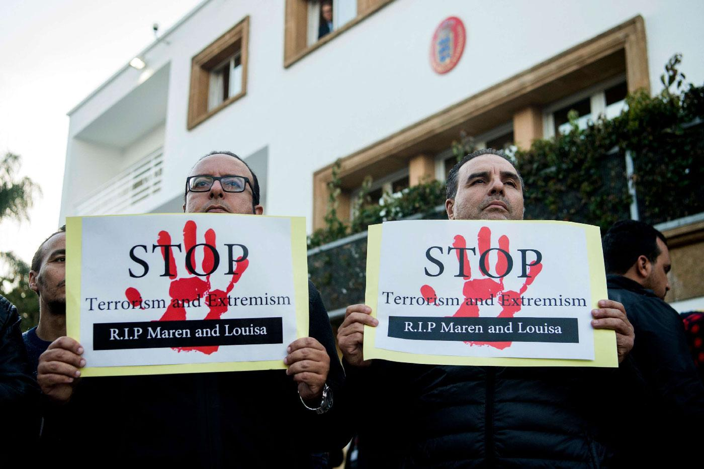 Moroccans holds placards as people pay tribute to murdered Danish Louisa Vesterager Jespersen and Norwegian Maren Ueland in Rabat, in front the Danish ambassy on December 22, 2018.