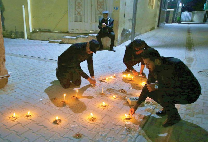Friends and relatives of Alaa Mashdhub light candles at his assassination site in Karbala, February 5