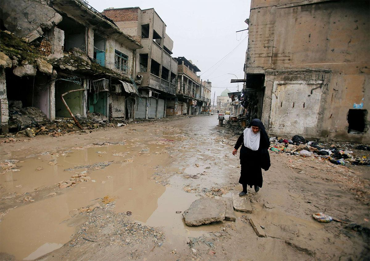 A woman walks next to damaged shops in the Old City of Mosul